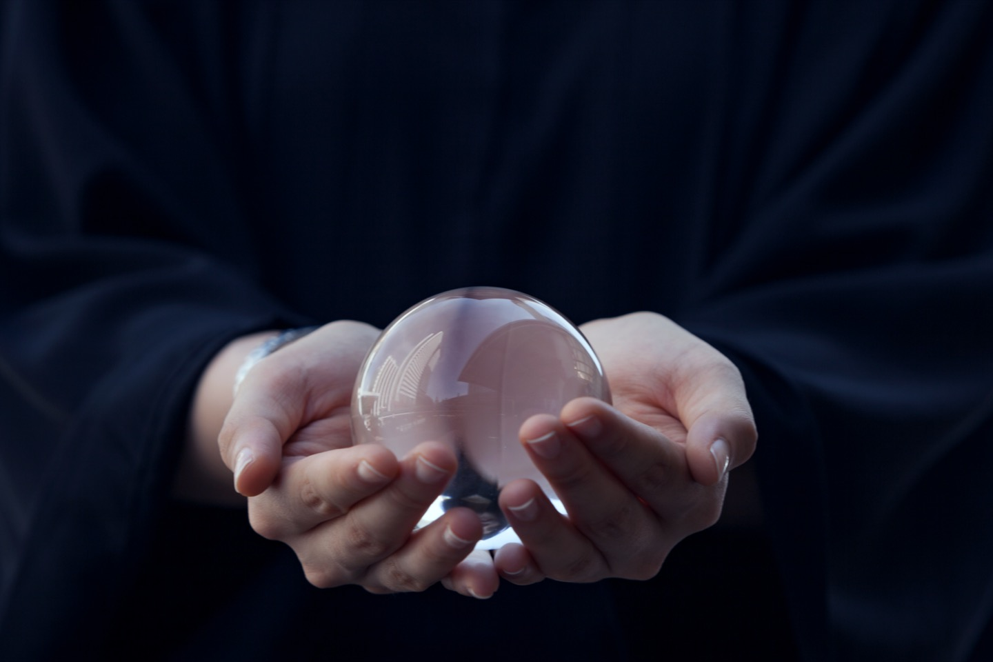 hands holding a glass ball